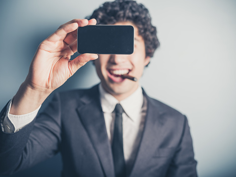 Young businessman smoking cigar and taking a selfie