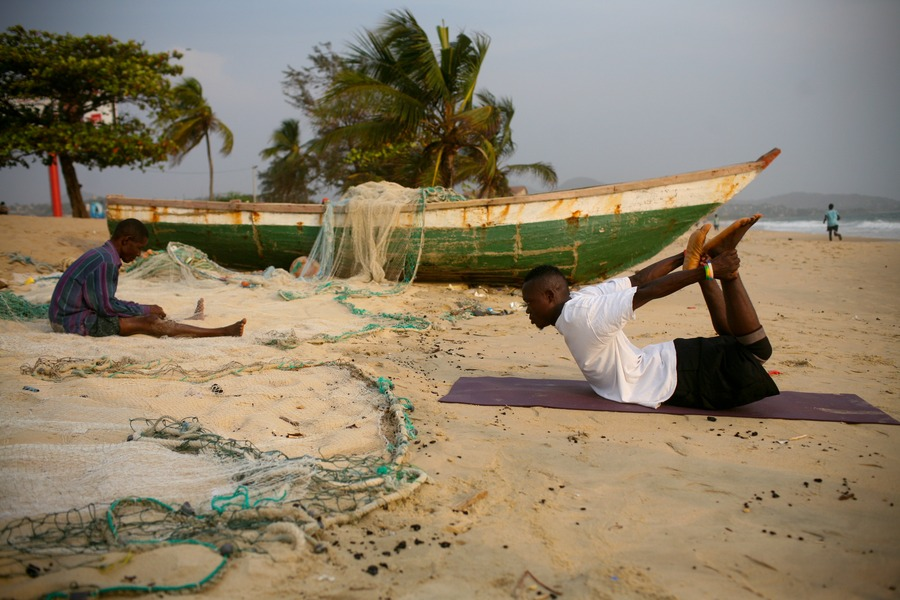 A member of Yoga Strength practices boat pose on Lumley Beach, Freetown. Charlotte Kesl/Yoga Strength, 2013.