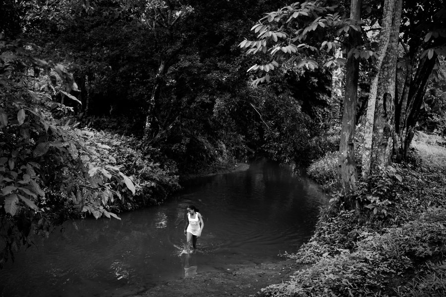 A young girl walks through the river in the Cacarica River Basin, in remote northeastern Colombia. Charlotte Kesl/Peace Brigades International, 2010.