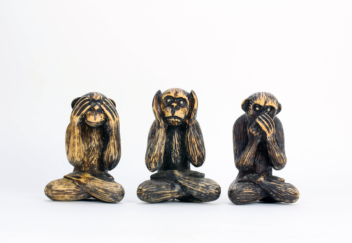 Old proverb carved out in three small monkeys - shot against a white background.